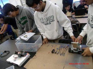 Group of robotic students are working hard to get their robot done.