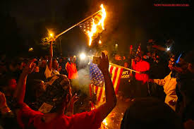 Angry protesters burning The United States flag.