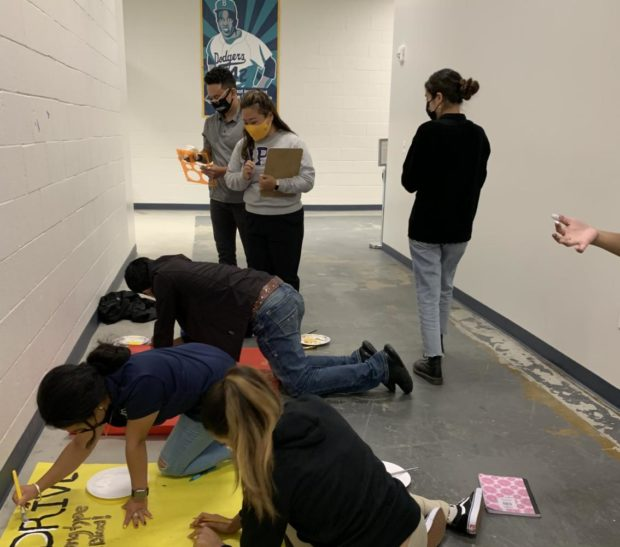 Students working on posters on the floor. Ms. Lee overseeing student work.